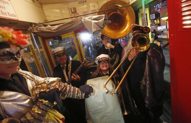 """The Elysian Brass Band performs as members of the """"Societe des Champs Elysee"""" ride the Rampart-St. Claude street car line, which just opened last fall, to commemorate the official start of Mardi Gras season, in New Orleans, Friday, January 6, 2017. (Photo by Gerald Herbert/AP Photo)"""