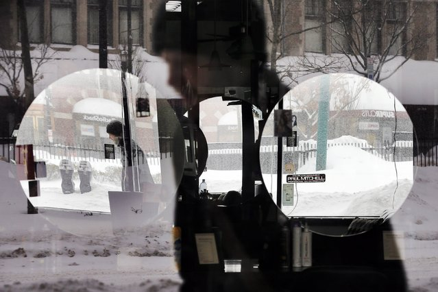 A pedestrian is reflected in the window and mirrors of a hair salon during a winter snow storm in Brookline, Massachusetts February 9, 2015. (Photo by Brian Snyder/Reuters)