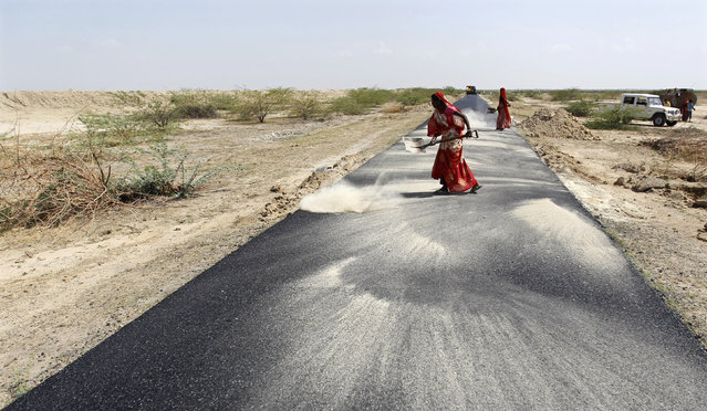 Women labourers throw dust on a road tarmac under construction at Bharadva village in Gujarat April 23, 2013. (Photo by Amit Dave/Reuters)
