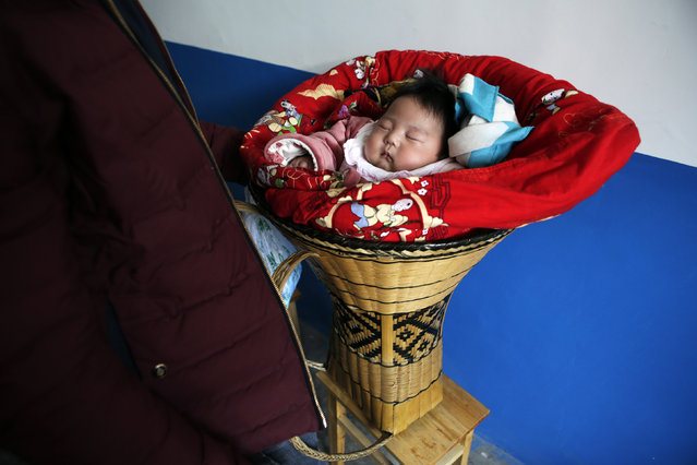 A 3-month-old ethnic Tujia baby girl is pictured next to her father as they wait for a traditional ethnic Tujia wedding feast during celebrations marking the Lunar New Year in Ziqiu town, Changyang county of China's Hubei province, February 15, 2016. (Photo by Jason Lee/Reuters)