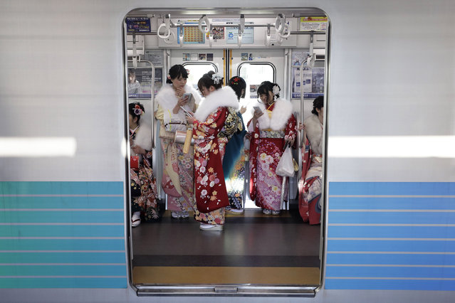 "Young Japanese women dressed in colorful kimonos use their smartphones on a train after attending a ceremony marking the ""Coming of Age Day"" at the Toshimaen Amusement Park, in Tokyo, Japan, 09 January 2017. The Coming of Age Day is the day to celebrate and encourage the youth who have reached the age of 20, which is considered the beginning of adulthood. (Photo by Kiyoshi Ota/EPA)"
