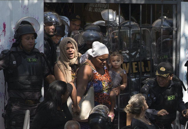 Women and children leave a building they invaded about a week ago as police evict them in the Flamengo neighborhood of Rio de Janeiro, Brazil, Tuesday, April 14, 2015. (Photo by Silvia Izquierdo/AP Photo)