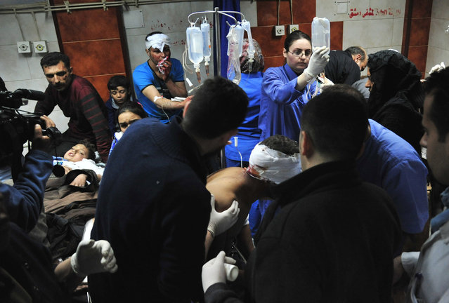 In this photo released by the Syrian official news agency SANA, doctors treat victims injured in the triple blast in Sayyida Zeinab, a predominantly Shiite Muslim suburb of the Syrian capital Damascus arrives to a hospital to receives treatment, Syria, Sunday, February 21, 2016. The Islamic State group claimed responsibility for a triple blast in the Shiite suburb, saying two IS fighters set off a car bomb before detonating their explosive belts and killing dozens. (Photo by SANA via AP Photo)