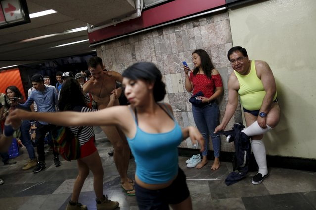 "A passenger takes off his pants as others not wearing pants dance while waiting for a subway train during the ""No Pants Subway Ride"" in Mexico City, Mexico, February 21, 2016. (Photo by Carlos Jasso/Reuters)"