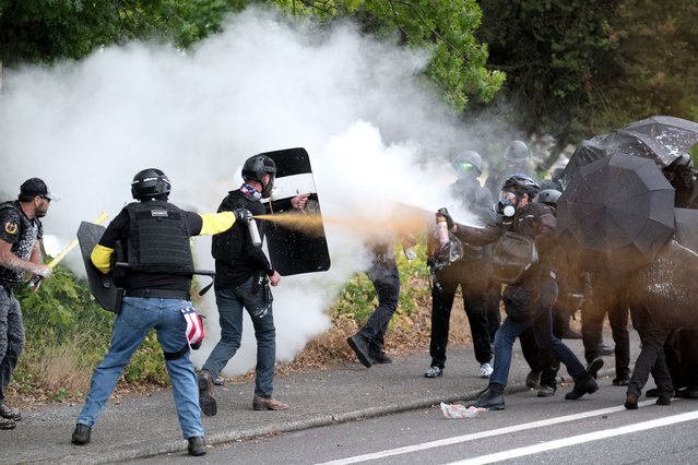 Members of the far-right group Proud Boys and anti-fascist protesters spray bear mace at each other during clashes between the politically opposed groups on Sunday, August 22, 2021, in Portland, Ore. (Photo by Alex Milan Tracy/AP Photo)