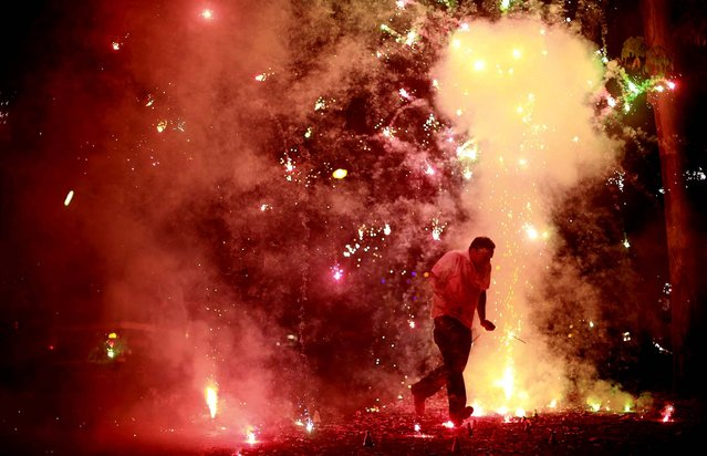 A man runs as firecrackers burst around him during the New Year celebrations in Mumbai, India. (Photo by Rafiq Maqbool/Associated Press)
