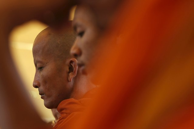 """Buddhist monks attend a Buddhist ceremony at Choeung Ek, a """"Killing Fields"""" site located on the outskirts of Phnom Penh, April 17, 2015. (Photo by Samrang Pring/Reuters)"""