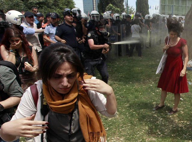 A Turkish riot policeman sprays tear gas as people protest against the destruction of trees in a park brought about by a pedestrian project, in Taksim Square in central Istanbul, Turkey, on May 28, 2013. (Photo by Osman Orsal/Reuters)