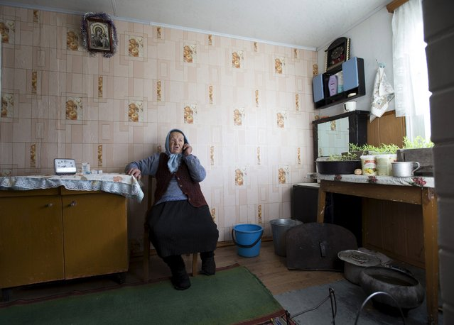 Nastia Pokolo, 74, speaks on a mobile phone at her house in the village of Babinets, southwest of the capital Minsk, April 17, 2015. (Photo by Vasily Fedosenko/Reuters)