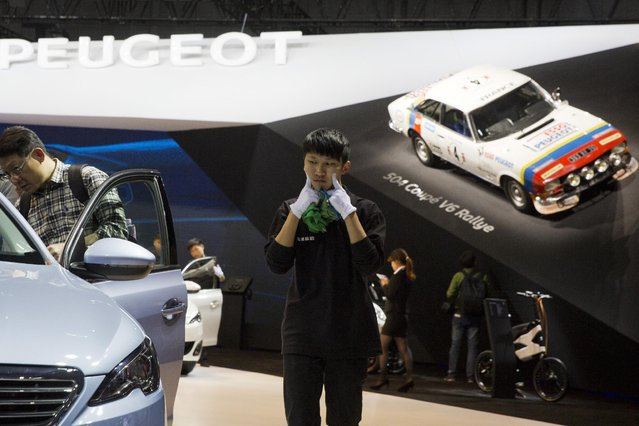 A worker pokes his cheeks as he works at the booth for Peugeot at the Shanghai Auto Show in Shanghai, Monday, April 20, 2015. Ford showed off its new Taurus and Nissan unveiled a midsize sedan designed for China on Monday at a Shanghai Auto Show that highlighted the commercial resurgence of lower-priced Chinese auto brands. (Photo by Ng Han Guan/AP Photo)