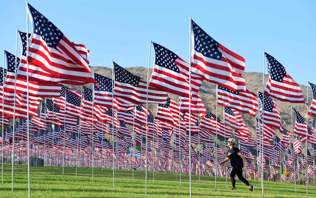A woman walks past a display of US flags to commemorate the 20th anniversary of 9/11 with the annual Waves of Flags display and remembrance at Pepperdine University in Malibu, California on September 8, 2021. For the fourteenth year, the university situated next to the Pacific Coast Highway along the Pacific Ocean, is commemorating the event by flying some 3,000 American flags, including international flags for each foreign country that lost a citizen in the attack. (Photo by Frederic J. Brown/AFP Photo)
