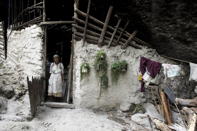 Francisca Gomez stands at the entrance of her home, a cave where she has been living for the past 50 years, in the mountains on the outskirts of Chusmuy April 21, 2015. (Photo by Jorge Cabrera/Reuters)