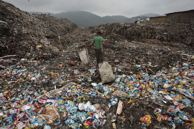 An Indian boy pulls a bag filled with recyclable material at a garbage dump yard in Gauhati, India, Wednesday, April 22, 2015. The world marks Earth Day on April 22 to increase awareness and to promote practices for the sustainability and protection of the Earth's natural environment. (Photo by Anupam Nath/AP Photo)