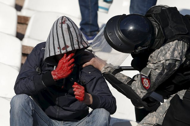 An injured fan is helped by a riot policeman during clashes between Red Star Belgrade and Partizan Belgrade fans in the stadium before the teams' Serbian Superliga soccer match in Belgrade, April 25, 2015. (Photo by Marko Djurica/Reuters)