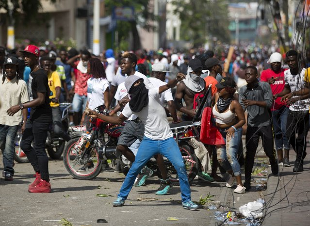 A demonstrator throws rocks at a house during a protest to demand the resignation of President Jovenel Moise and demanding to know how Petro Caribe funds have been used by the current and past administrations, in Port-au-Prince, Haiti, Thursday, February 7, 2019. (Photo by Dieu Nalio Chery/AP Photo)