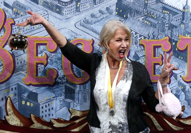 Actress Helen Mirren holds the Hasty Pudding Pot aloft during her roast as woman of the year by Harvard University's Hasty Pudding Theatricals in Cambridge, on January 30, 2014. (Photo by Associated Press)