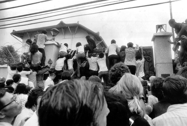 In this April 30, 1975 file photo, South Vietnamese civilians try to scale the walls of the U.S. embassy in Saigon in an attempt to get aboard evacuation flights. (Photo by Neal Ulevich/AP Photo)