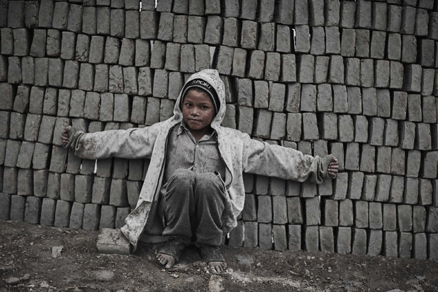 A dust covered young boy spreads his arms out as he leans against a mound of bricks in Kathmandu Valley, Nepal, 18 January 2014. (Photo by Jan Moeller Hansen/Barcroft Images)