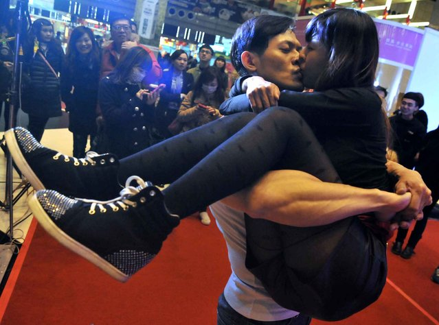 A couple take part in a kissing competition to celebrate Valentine's day in the Taipei Train Station on February 14, 2014. Valentine's day and the Lantern Festival are celebrated on the same date this year as the festival is celebrated on the fifteenth day of the first month in the lunar year in the Chinese calendar. (Photo by Mandy Cheng/AFP Photo)