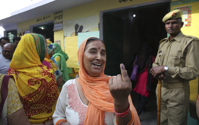 A woman shows the indelible ink mark on her index finger after casting her vote at a polling booth for the first phase of general elections, near Ghaziabad, India Thursday, April 11, 2019. Voters in 18 Indian states and two Union Territories began casting ballots on Thursday, the first day of a seven-phase election staggered over six weeks in the country of 1.3 billion people. (Photo by Manish Swarup/AP Photo)