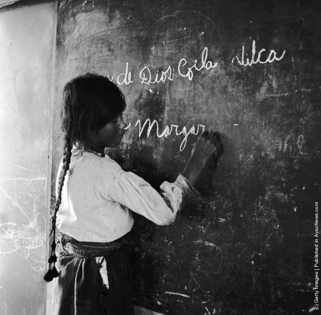A schoolgirl writes at the blackboard in an Adventist school on the reed island of Urso, on Lake Titicaca, Peru, 1950