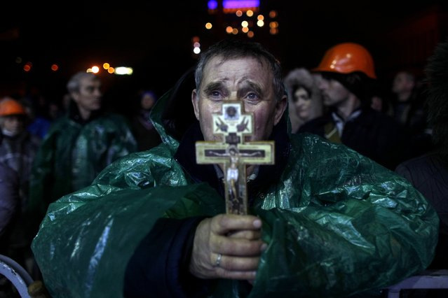 "An anti-government protester holds a crucifix as he prays at Independence Square in Kiev, Ukraine, Thursday, February 20, 2014. Ukraine's protest leaders and the president they aim to oust called a truce Wednesday, just hours after the military raised fears of a widespread crackdown with a vow to defeat ""terrorists"" responsible for seizing weapons and burning down buildings. (Photo by Marko Drobnjakovic/AP Photo)"
