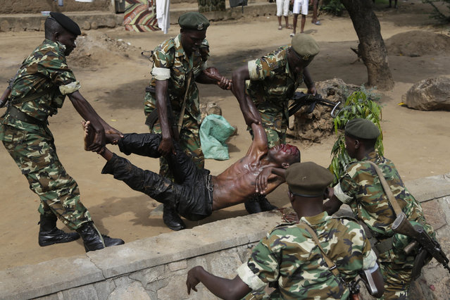 Soldiers lift a wounded suspected Imbonerakure militiaman who was attacked by demonstrators protesting against President Pierre Nkurunziza's decision to seek a third term in office in the Cibitoke district of Bujumbura, Burundi, Thursday May 7, 2015. (Photo by Jerome Delay/AP Photo)