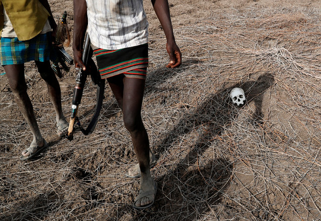 Turkana warriors pass by a skull of a Dassenach warrior who was, according to a Turkana warrior, killed when he tried to ambush Turkana cattle herders in Ilemi Triangle, Kenya on March 26, 2019. (Photo by Goran Tomasevic/Reuters)