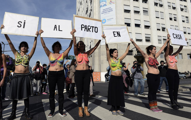"""Midwives and pregnant women show their painted breasts during a demonstration in Buenos Aires on May 14, 2015 against the scheduled new policy of the Healt Minister to regulate home natural births. The signs read """"Yes to home birth"""". (Photo by Juan Mabromata/AFP Photo)"""