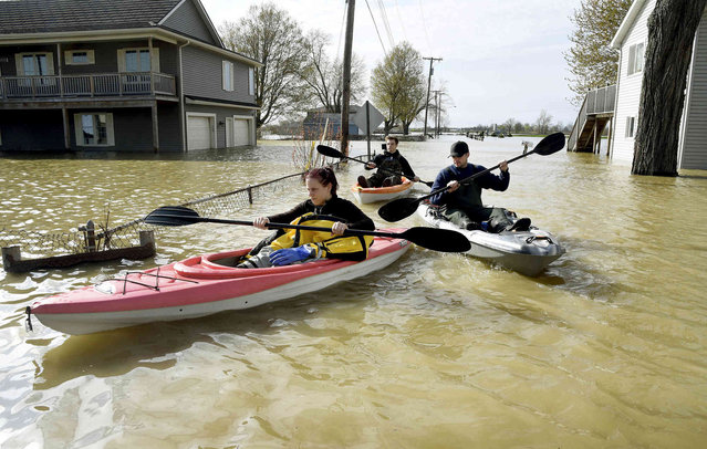 In this Wednesday, May 8, 2019 photo, Estral Beach Firefighters Courtney Millar, Eric Bruley, and Chase Baldwin kayak down Lakeshore Dr. in the south end of Estral Beach in Berlin Township, Mich., to see if anyone needs to be evacuated while also checking the floodwaters. Wind-driven water caused more flooding in southeastern Michigan along western Lake Erie following recent rainfall that contributed to high water levels in the Great Lakes. (Photo by Tom Hawley/The Monroe News via AP Photo)