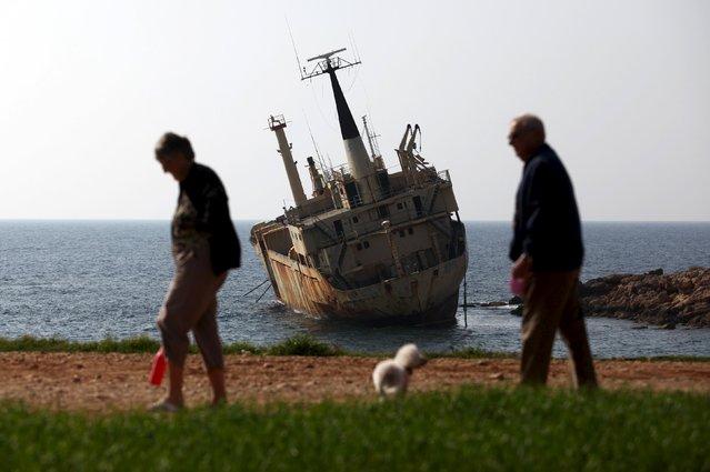 Tourists walk near a shipwreck in the coastal village of Pegeia, Cyprus February 28, 2016. (Photo by Yiannis Kourtoglou/Reuters)