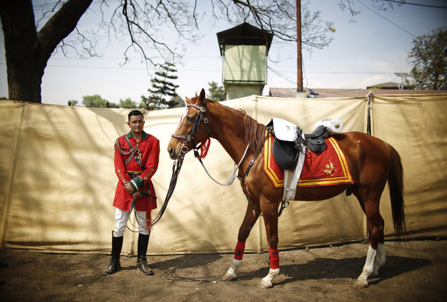 "A Nepalese army solder stand next to a horse during the ""Ghodejatra"" Horse Race festival, which is organised by the Nepal Army, in Kathmandu, Nepal, April 7, 2016. Ghode Jatra, the horse racing festival of Nepal, celebrated on the New Moon day of mid March or early April is among the important celebrations of the Kathmandu Valley. exists a tree in the South-East part of the Tundikhel where Gurumapa supposed to be resides. (Photo by Navesh Chitrakar/Reuters)"