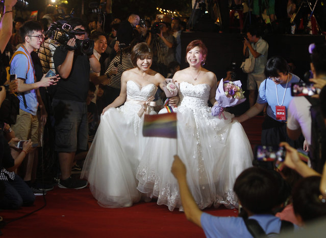 Taiwanese same-s*x couples walk the red carpet at their wedding party in Taipei, Taiwan, Saturday, May 25, 2019. Taiwan became the first place in Asia to allow same-s*x marriage last week. Hundreds of same-s*x couples in Taiwan rushed to get married Friday, the first day a landmark decision that legalized same-s*x marriage took effect. (Photo by Chiang Ying-ying/AP Photo)