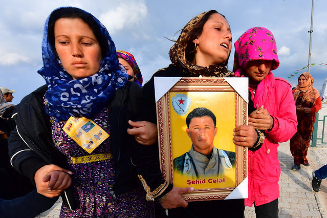 Relatives of a fighter of the Syrian Democratic Forces (SDF) who were killed in an attack claimed by the Islamic State (IS) group in Manbij walk with his portrait during a funeral for the attack victims in the northern Syrian-Kurdish town of Kobane on March 27, 2019. Manbij is a former IS stronghold that is now ruled by a military council affiliated with the Syrian Democratic Forces (SDF), the US-backed Kurdish-led alliance that declared victory over IS in its last redoubt in eastern Syria on Saturday. (Photo by Giuseppe Cacace/AFP Photo)