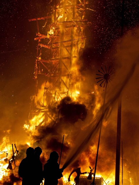 """Some firemen wet the trees near a Moses statue """"falla"""" of Town Hall square for the """"crema"""", the moment in which more than three hundred """"fallas"""" starts to burn, celebrating Saint Joseph's night during Las Fallas Festival at Town Hall square in Valencia. (Photo by Manuel Bruque/EPA)"""