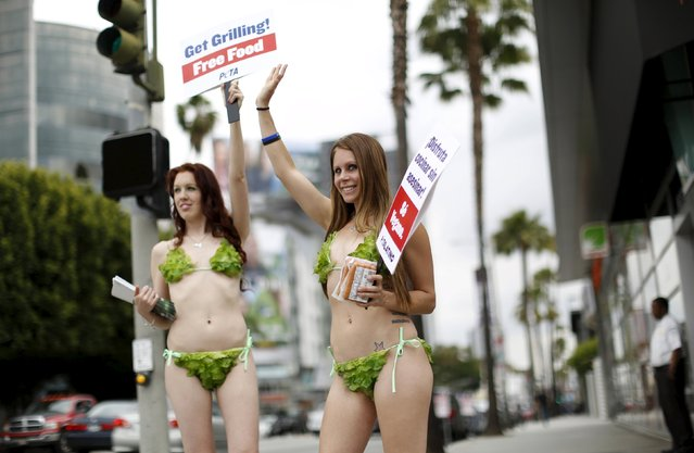 Activists Kimberly Moffatt (R) and Meggan Anderson from People for the Ethical Treatment of Animals (PETA) hold signs promoting a vegan diet in Los Angeles, California May 21, 2015. (Photo by Mario Anzuoni/Reuters)