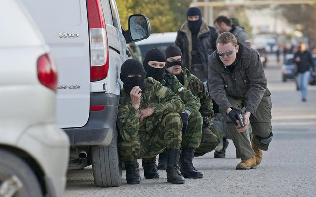 Pro Russian Militia people hide themselves behind cars as they secure the road to the Belbek airbase outside Sevastopol, Crimea, on Saturday, March 22, 2014. Russian forces used at least four armored vehicles to break into an air base here, seizing control of one of the last Ukrainian military outposts in Crimea. (Photo by Andrew Lubimov/AP Photo)
