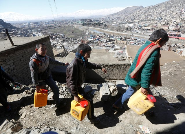 Afghan boys carry water they as they climb a hill in Kabul, Afghanistan February 20, 2017. (Photo by Omar Sobhani/Reuters)