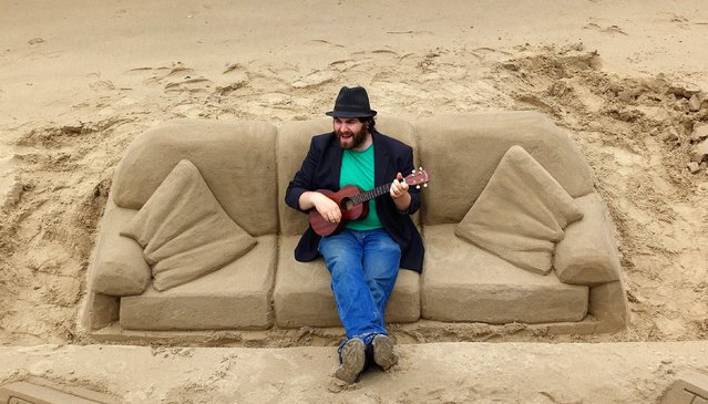 Luc Valvona sings as he plays the ukulele while sitting on a couch made of sand along the south bank of the River Thames Saturday, May 23, 2015, in London. (Photo by Ross D. Franklin/AP Photo)