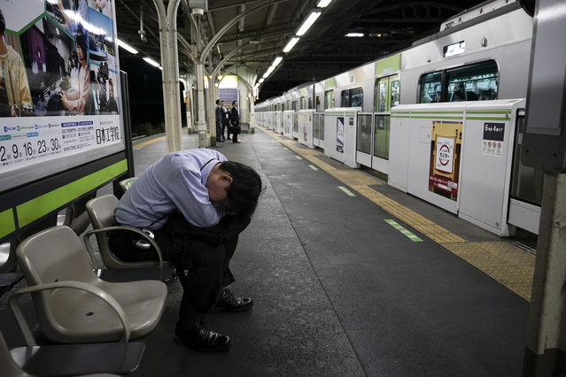 In this Saturday, May 25, 2019, photo, a commuter falls asleep on a platform as a Yamanote Line train departs in Tokyo. Want to take a glimpse of daily life in downtown Tokyo? Take a ride on the Yamanote loop line. For most Tokyoites, the line means an incredibly punctual and efficient transportation system for commuting. For tourists, it offers a glimpse into the life of ordinary people living in the city. (Photo by Jae C. Hong/AP Photo)