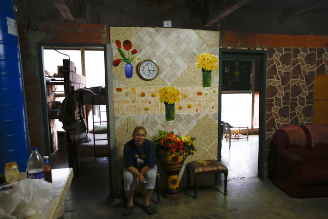 """Adriana Gutierrez sits in the living of her 24th floor apartment inside the """"Tower of David"""" skyscraper in Caracas February 3, 2014. (Photo by Jorge Silva/Reuters)"""