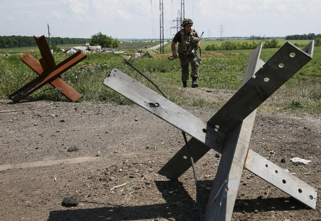 """A member of the Ukrainian armed forces is seen near the town of Maryinka, eastern Ukraine, June 5, 2015. Ukraine's president told his military on Thursday to prepare for a possible """"full-scale invasion"""" by Russia all along their joint border, a day after the worst fighting with Russian-backed separatists in months.  REUTERS/Gleb Garanich"""