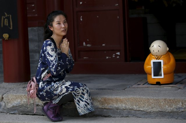 A visitor asks a temple staff to give her chance to take picture with robot Xian'er which is placed in the main building of Longquan Buddhist temple for photograph, on the outskirts of Beijing, April 20, 2016. (Photo by Kim Kyung-Hoon/Reuters)