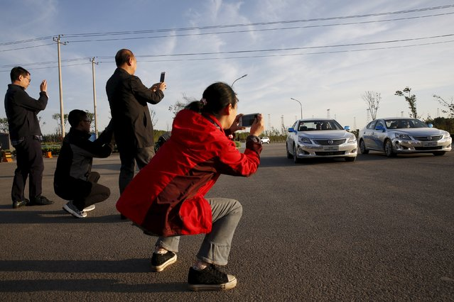 Visitors take pictures of Changan Automobile's self-driving cars, which are manually driven, as they complete a test drive from Chongqing to Beijing to arrive at Changan Automobile's Beijing headquarters, China, April 16, 2016. (Photo by Kim Kyung-Hoon/Reuters)