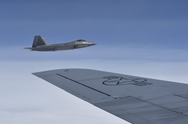 A U.S. F-22 Raptor fighter flies alongside a KC-135 refueling plane over European airspace, during a flight from Britain to Mihail Kogalniceanu air base in Romania April 25, 2016. (Photo by Toby Melville/Reuters)