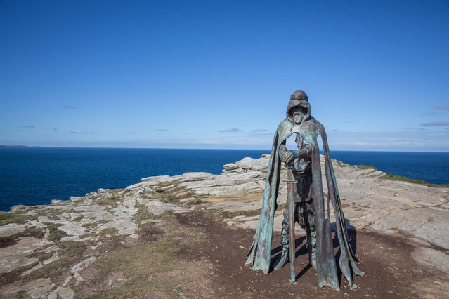 """The new """"Gallos"""" sculpture that has been erected at Tintagel Castle is seen in Tintagel on April 28, 2016 in Cornwall, England. The English Heritage managed site and the nearby town have long been associated with the legend of King Arthur and continue to attract large visitor numbers. However, efforts by English Heritage to update the visitor experience with the Gallos sculpture, along with a rock carving of Merlin's face, which English Heritage say are inspired by the legend of King Arthur and Tintagel Castles royal past, have met with criticism from some Cornish nationalists and historians. (Photo by Matt Cardy/Getty Images)"""
