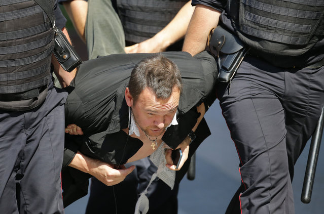Police officers detain a man during an unsanctioned rally in the center of Moscow, Russia, Saturday, July 27, 2019. Russian police on Saturday began arresting people outside the Moscow mayor's office ahead of an election protest demanding that opposition candidates be allowed to run for the Moscow city council. (Photo by Alexander Zemlianichenko/AP Photo)