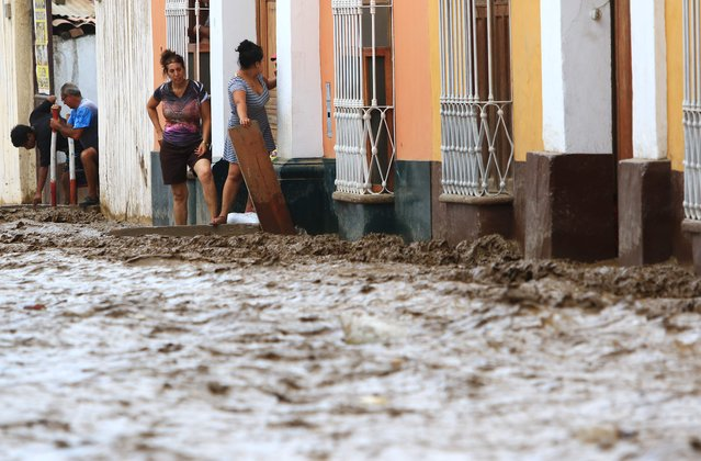 Local residents try to create a barrier as a flash flood hits the city of Trujillo, 570 kilometres north of Lima on March 18, 2017, bringing mud and debris. (Photo by Celso Roldan/AFP Photo)
