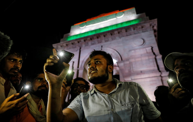 People hold their mobile phone torches as they take part in a protest demanding investigation in a highway collision in which a woman who is fighting a rape case against a legislator of the ruling Bharatiya Janata Party (BJP) was critically injured, in New Delhi, India, July 29, 2019. (Photo by Danish Siddiqui/Reuters)