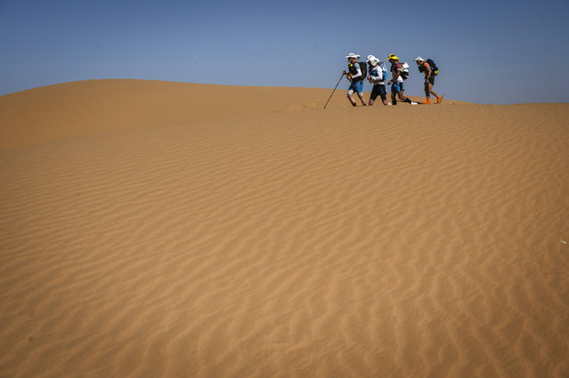People compete in the stage 2 of the 34th edition of the Marathon des Sables between Tisserdimine and Kourci Dial Zaid in the southern Moroccan Sahara desert, on April 8, 2019. The 34th edition of the marathon is a live stage 250 kilometres race through a formidable landscape in one of the world's most inhospitable climates. (Photo by Jean-Philippe Ksiazek/AFP Photo)